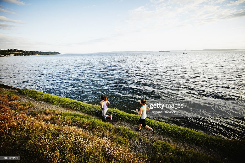 Two women running together on path near shoreline