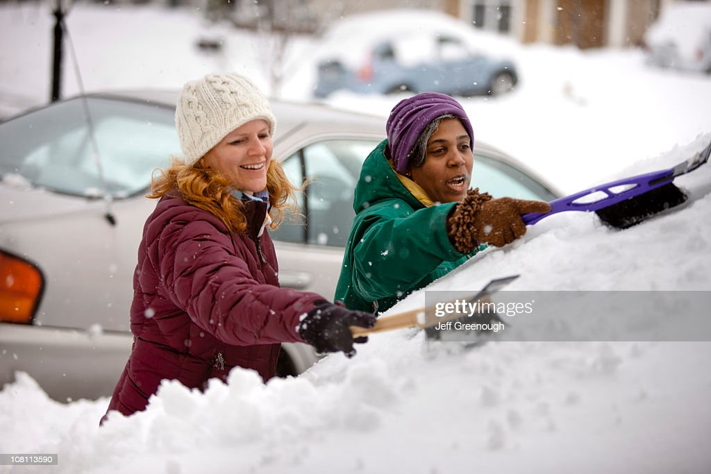 Two women scraping snow from windshield