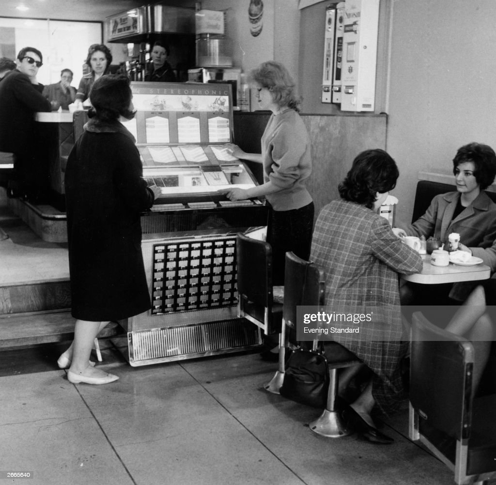 Two women selecting music from a jukebox in a coffee bar.