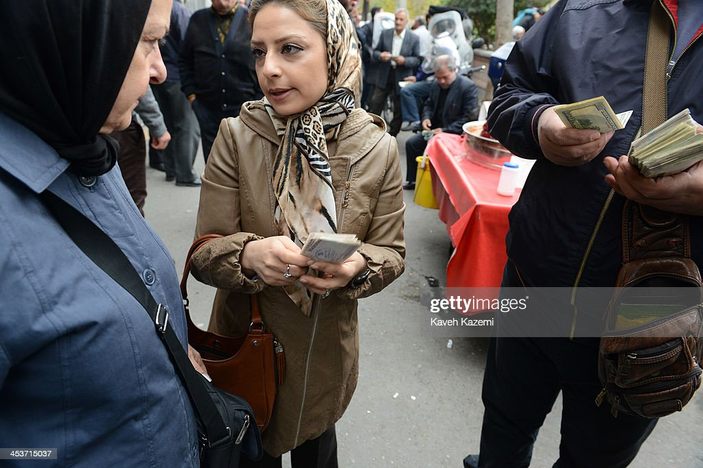 Two women sell US Dollars to a money changer holding a handful of Iranian Rials and US Dollar bills in his hand standing on the corner of Manouchehri street on November 19, 2013 in Tehran, Iran.