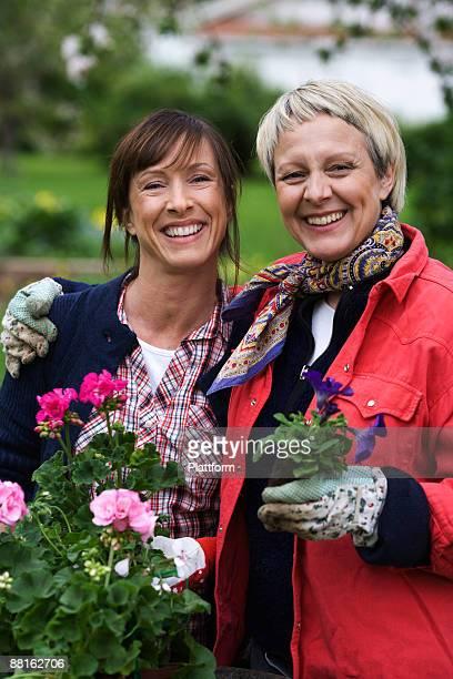Two women setting flowers in pots Sweden.