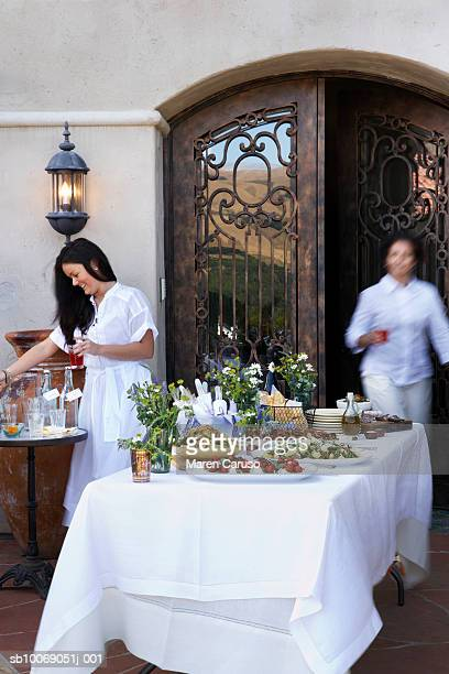Two women setting table of appetizers, wrought iron door in background