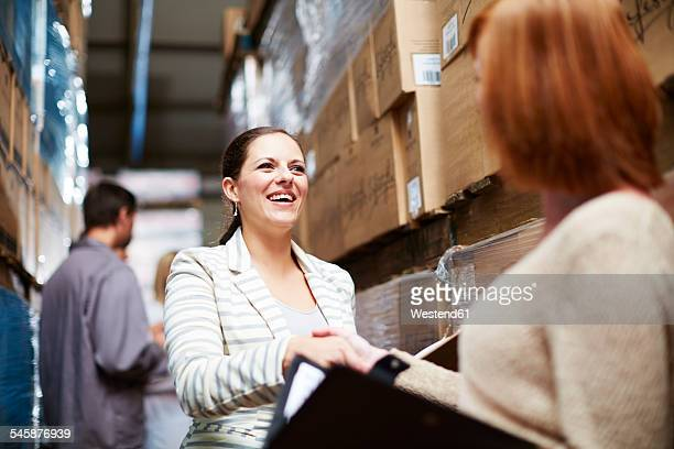 Two women shaking hands in warehouse