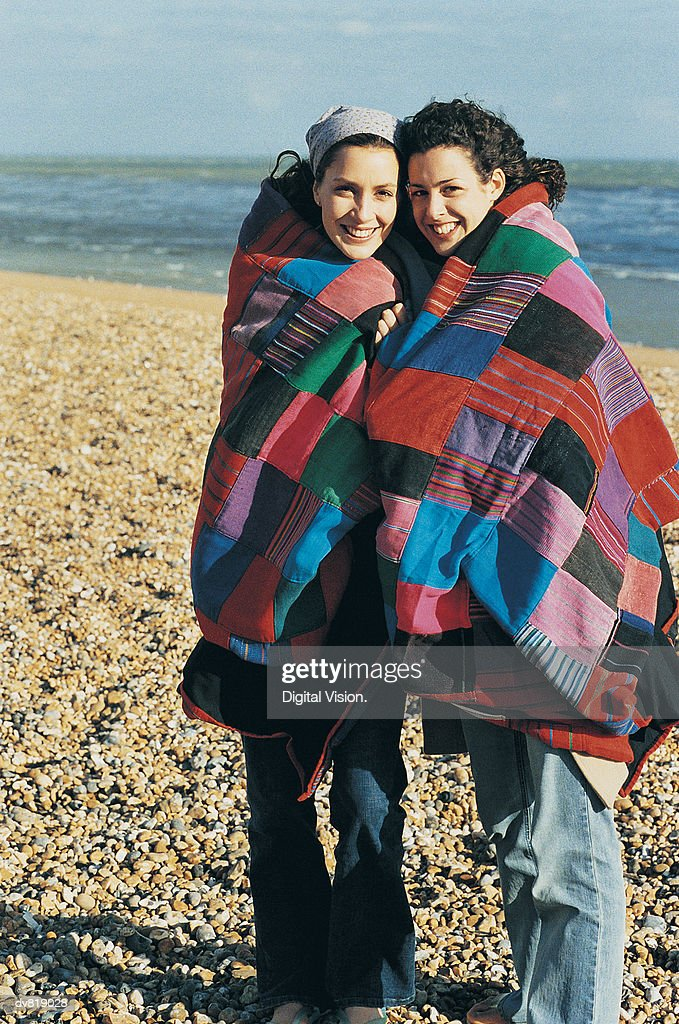 Two Women Sharing a Blanket at the Seaside : Stock Photo