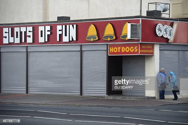 Two women shelter outside a shuttered amusement arcade from strong winds brought about by the remnants of Hurricane Gonzalo in Blackpool northwest...
