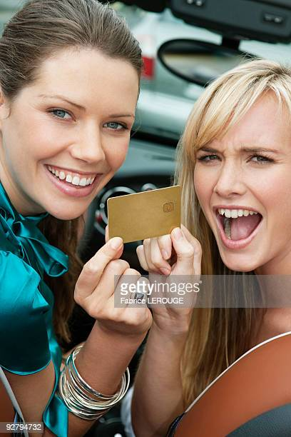 Two women showing a credit card in a car