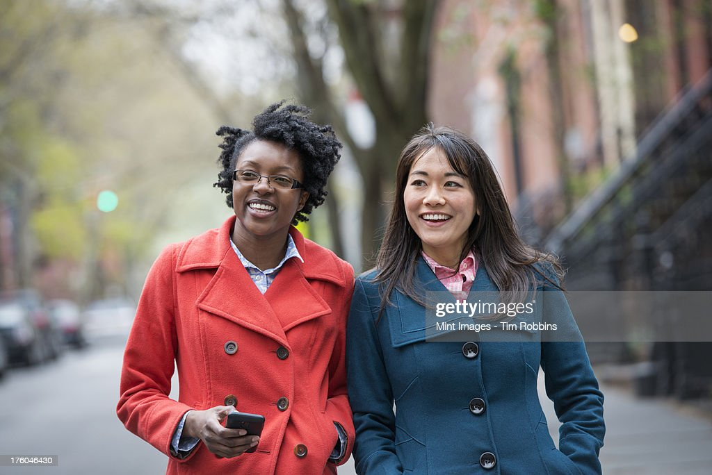 Two women side by side on a city street. One holding a cell phone. : Stock Photo