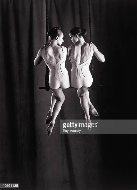 Two women side by side on trapeze, rear view (B&W)