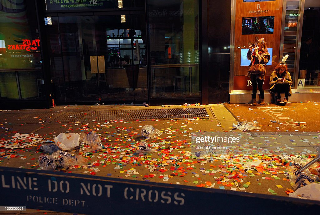 Two women sit and take photos outside of a hotel amidst confetti and debree left behind after thousands of revelers gathered in New York's Times Square to celebrate the ball drop at the annual New Years Eve celebration on December 31, 2011 in New York City.