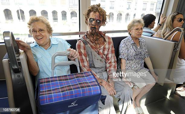 Two women sit next to an actor dressed up as zombie as they travel by tram on September 2 in the Northern Spanish city of Bilbao Actors and dancers...