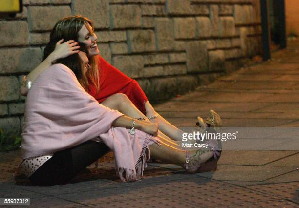Two women sit on the floor after leaving a club in Bristol City Centre on October 15 2005 in Bristol England Pubs and clubs preparing for the new...