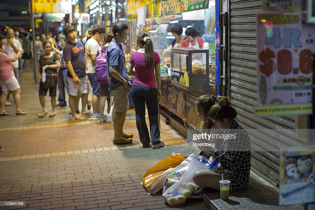 Two women sit outside a closed store in the Mong Kok district of Hong Kong, China, on Sunday, June 30, 2013. Hong Kongs best-selling newspapers called on readers to join a march to mark the anniversary of the citys handover to China, saying the government has failed to address issues of poverty and universal suffrage. Photographer: Jerome Favre/Bloomberg via Getty Images