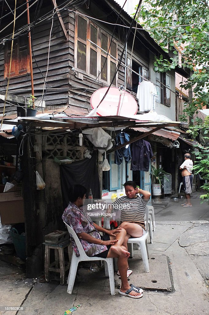 Two women sit under a roof where a satellite dish is installed in the Ban Batt community alleyway on October 25, 2012 in Bangkok, Thailand. Ban Batt community are the last remaining people still making Monk's Bowl in Bangkok.