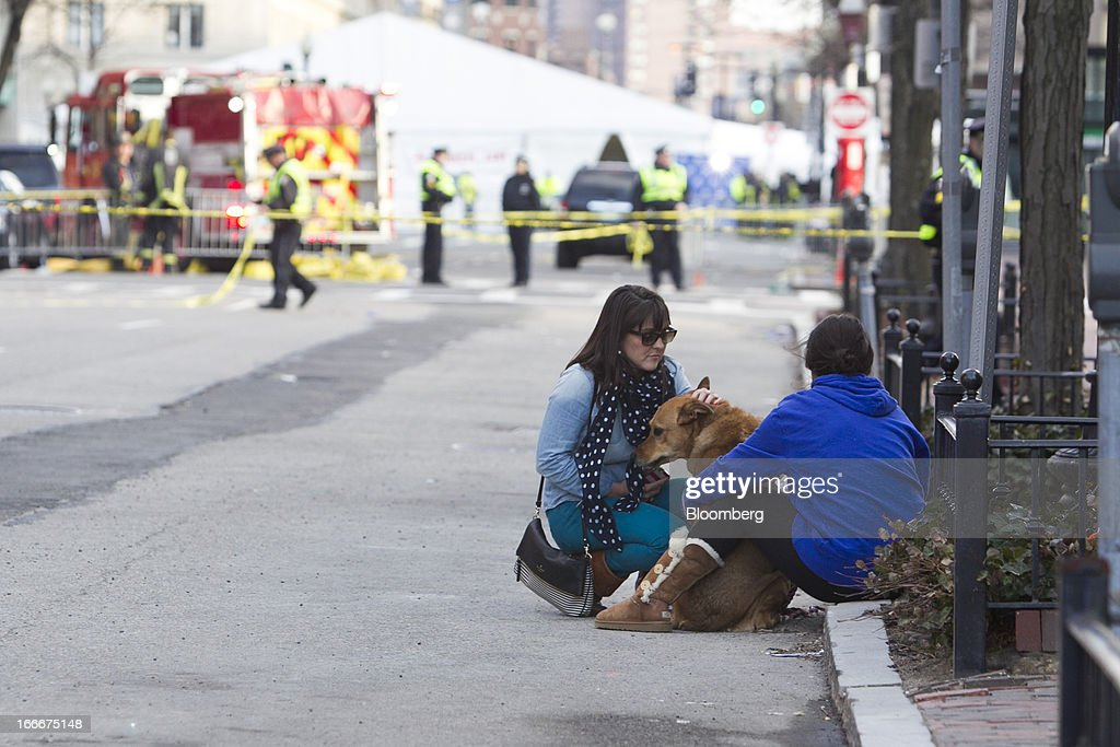 Two women sit with a dog along Dartmouth Street after two explosions occurred along the final stretch of the Boston Marathon on Boylston Street in Boston, Massachusetts, U.S., on Monday, April 15, 2013. Powerful bombs killed two people and injured scores near the finish of the Boston Marathon, turning one of the world's oldest road races into bloody chaos. Photographer: Kelvin Ma/Bloomberg via Getty Images