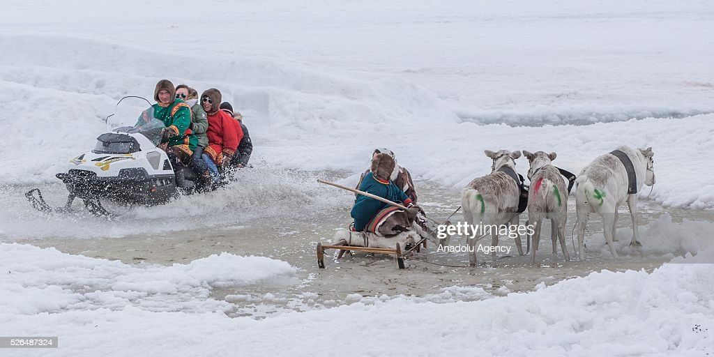 Two women sits on a reindeers' sled as a man rides snowmobile with three people at his back in melting snow at the north of Yamal Gyda, the northernmost settlement of the Yamalo-Nenets Autonomous Okrug in Russia on April 27, 2016. Effects of global warming are seen more clearly every year as north gets warmer and spring comes sooner. This situation makes residents and reindeer herders' life very difficult.