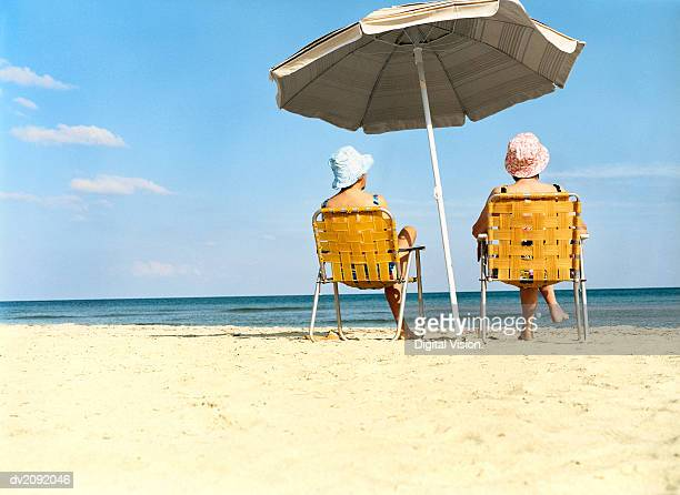 Two Women Sitting a Chairs Under a Parasol on the Beach
