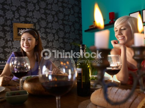 Two women sitting at dining table   Stock Photo db20b7261