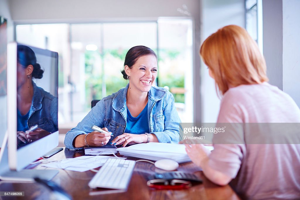 Two women sitting at home office table and working : Stock Photo