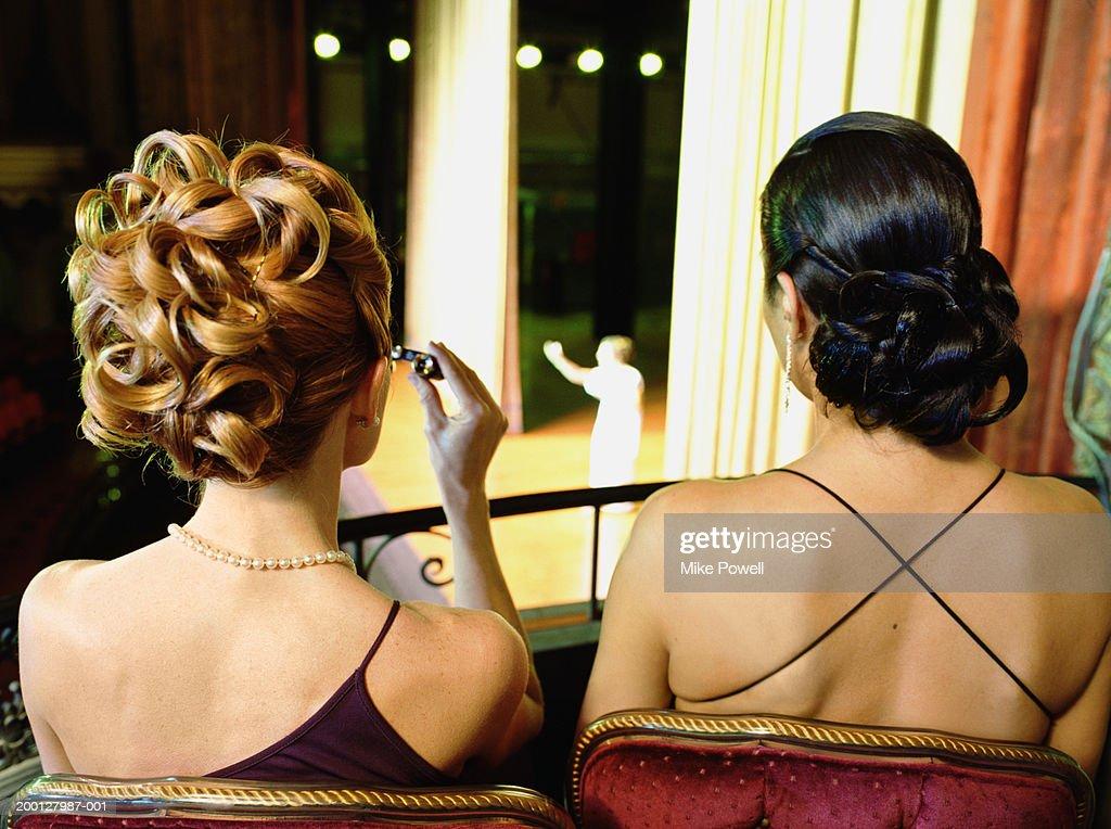 Two women sitting in balcony seats at opera, rear view