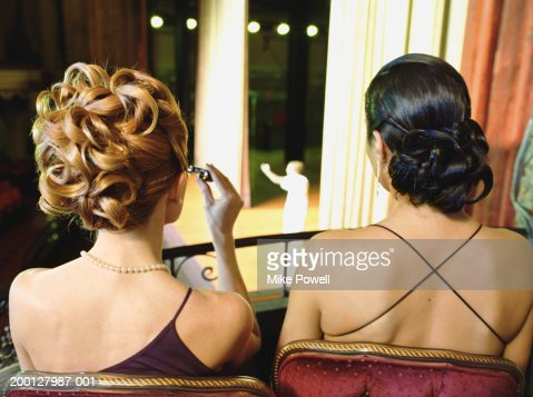 Two women sitting in balcony seats at opera, rear view