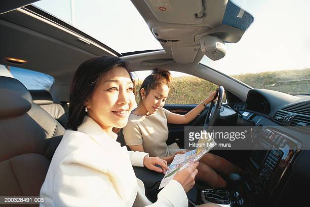 Two women sitting in car, looking at map, elevated view, close up
