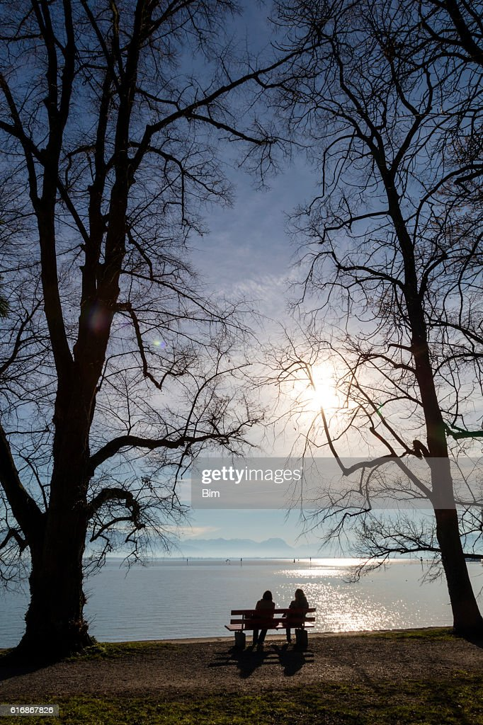 Two women sitting on a bench by the lake : Stock Photo