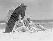 Two women sitting on beach under parasol.