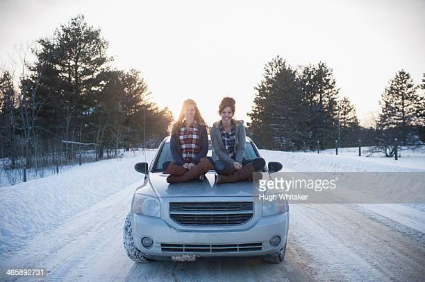 Two women sitting on car bonnet in snow