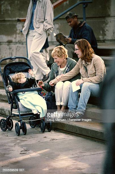 Two women sitting on steps, looking at baby boy (6-9 months) in pram