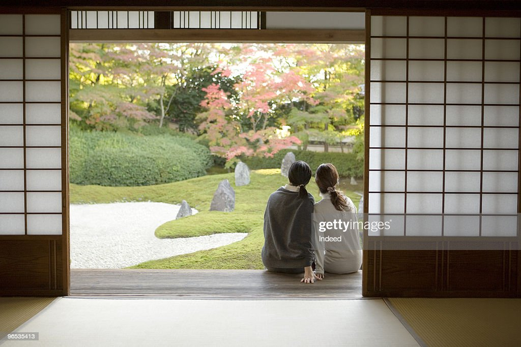 Two women sitting on the porch, close together