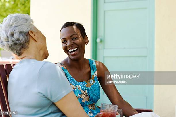 Two women sitting outdoors on wooden bench laughing