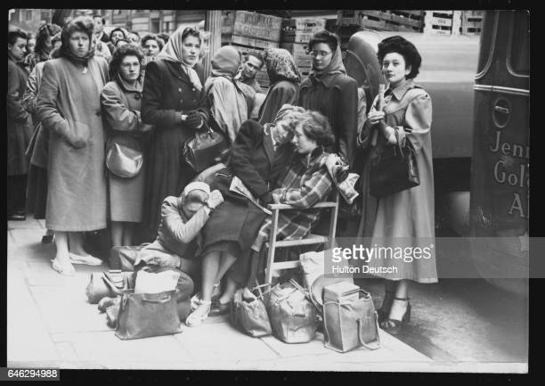 Two women sleep in a chair at the front of a queue for tickets outside the London Palladium The women have been queuing all night to buy standing...