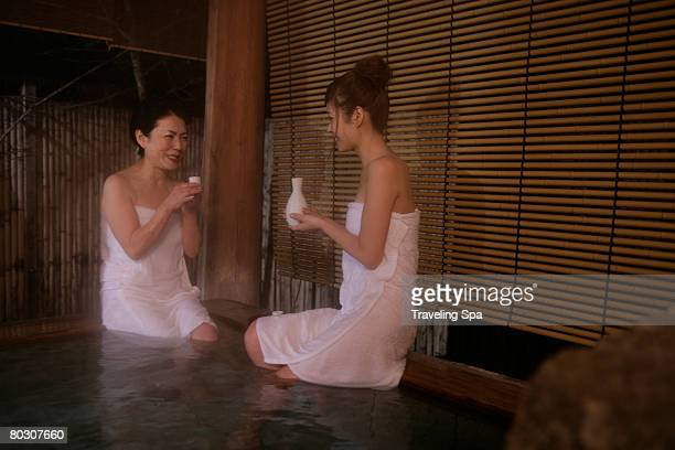Two women soaking in hot tub, drinking sake