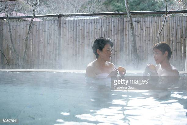 Two women soaking in hot tub, holding oranges