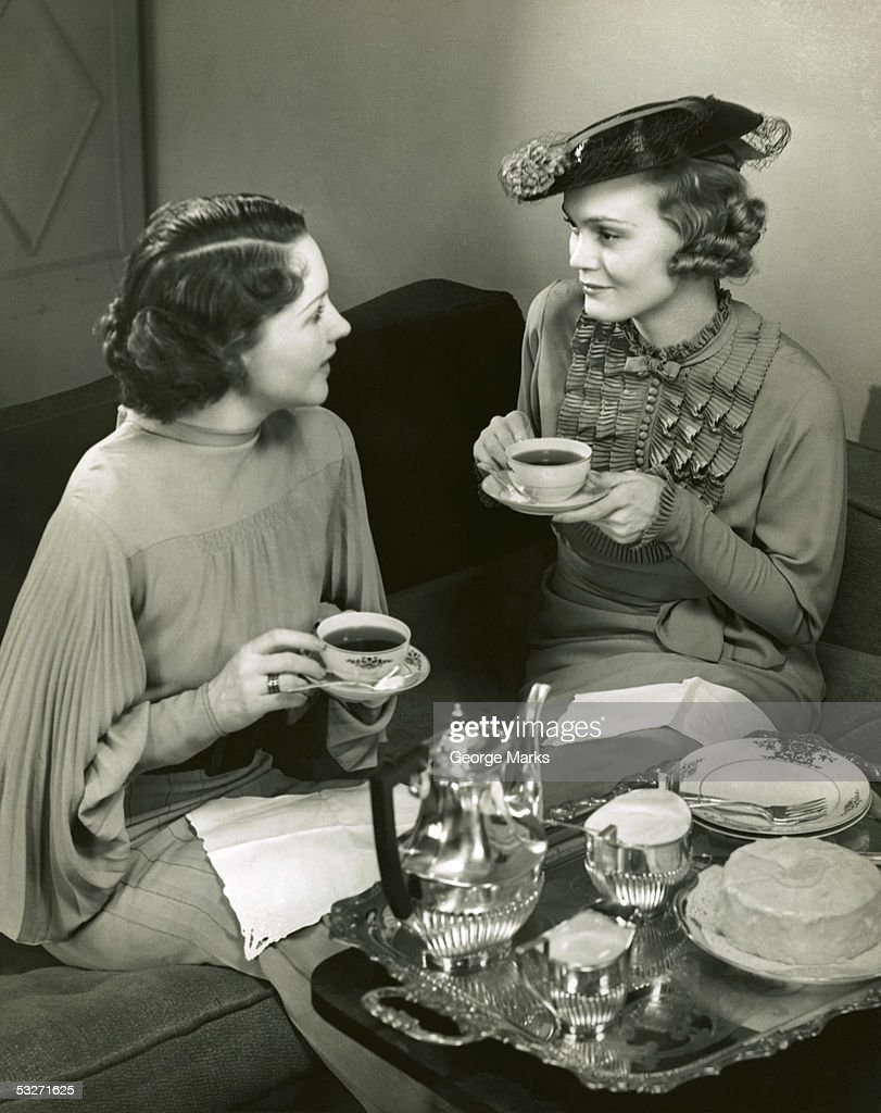 Two women socializing and drinking tea : Stock Photo