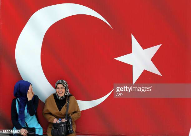 Two women speak in front of a Turkish flag in Ankara on April 6 ten days ahead of the referendum on whether to change the current parliamentary...