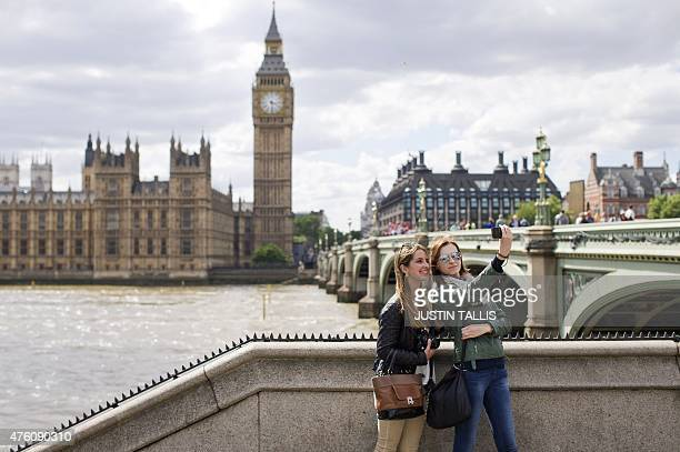 Two women stand by a wall on the bank of the River Thames as they pose for a 'selfie' photograph opposite the Elizabeth Tower home to Big Ben and the...