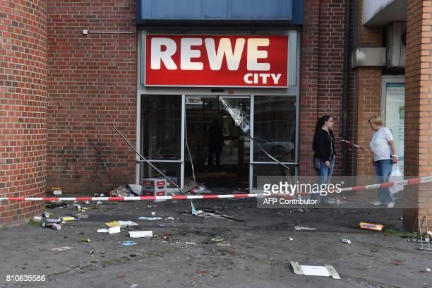 Two women stand in front of a destroyed Rewe City supermarket after riots in Hamburg's Schanzenviertel district on July 8 2017 in Hamburg northern...