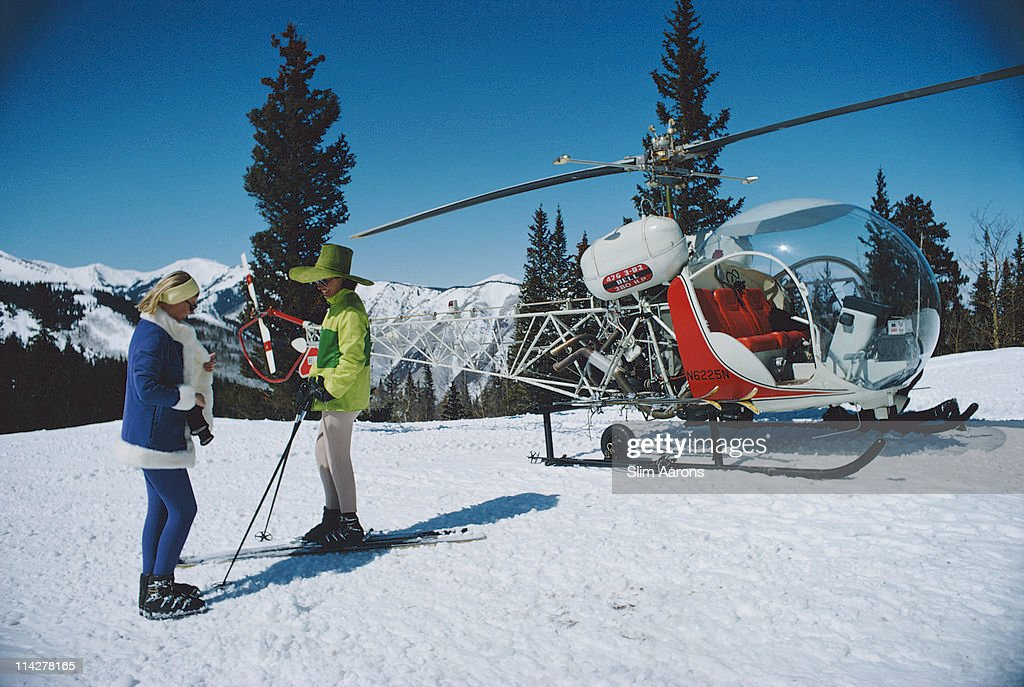 Two women stand in the foreground of a snowy landscape with a helicopter on the slopes of Snowmass Village in Pitkin County Colorado in March 1968