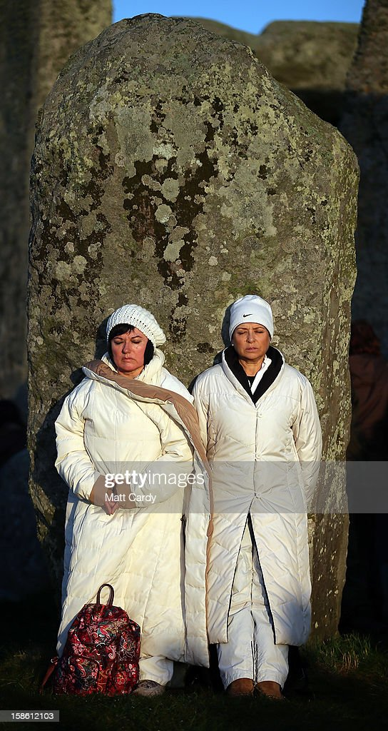 Two women stand in the stone circle as the sun rises, as druids, pagans and revellers take part in a winter solstice ceremony at Stonehenge on December 21, 2012 in Wiltshire, England. Predictions that the world will end today as it marks the end of a 5,125-year-long cycle in the ancient Maya calendar, encouraged a larger than normal crowd to gather at the famous historic stone circle to celebrate the sunrise closest to the Winter Solstice, the shortest day of the year.