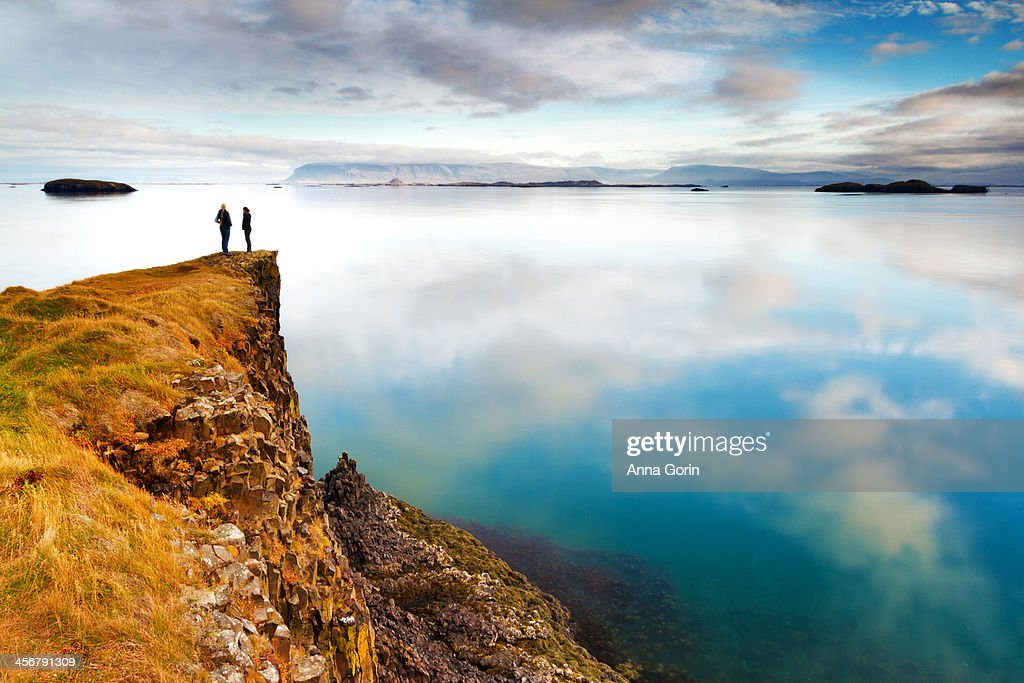 Two women stand on cliff overlooking calm bay