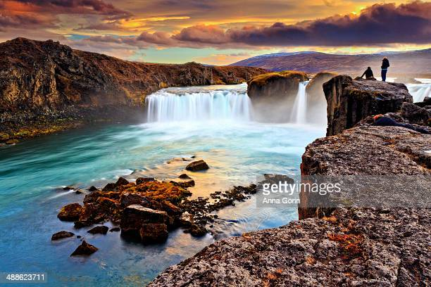Two women stand on cliffs above Godafoss at sunset