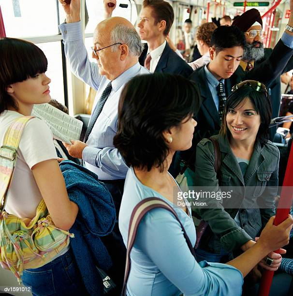 Two Women Stand Talking on a Crowded Passenger Train