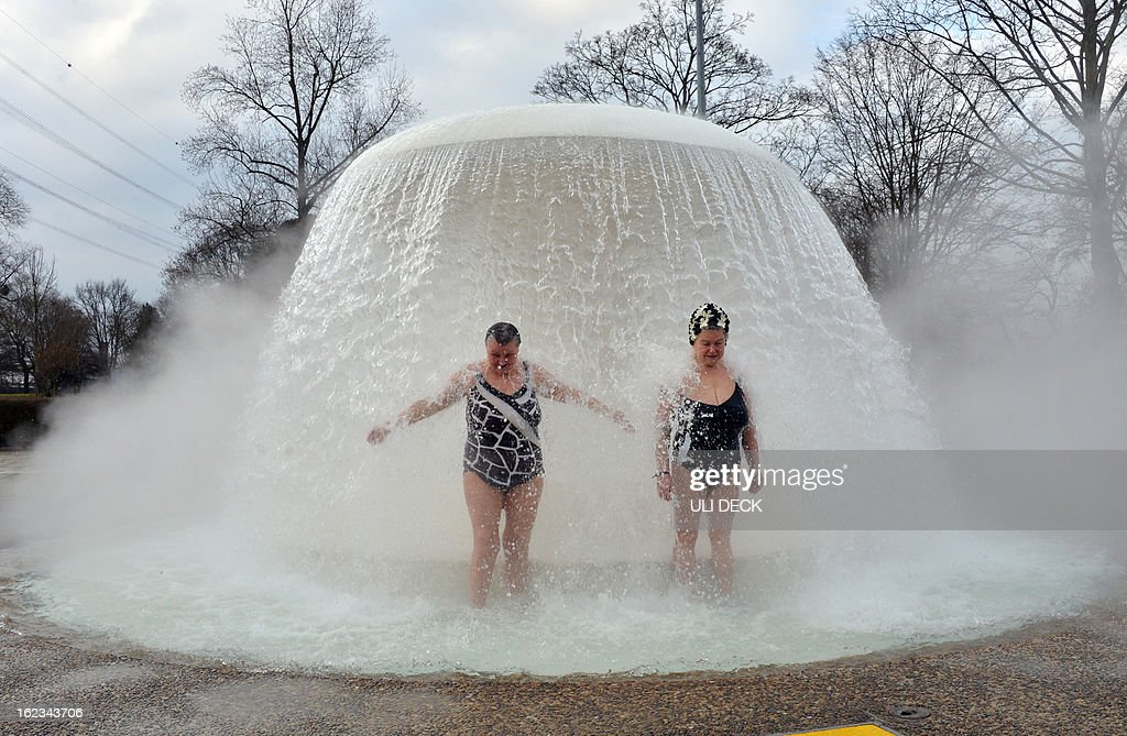 Two women stand under a fountain in the so-called 'Sonnenbad' (Sun bath) swimming pool at temperatures just below 0 degrees Celsius during the opening of the pool for the new season Karlsruhe, southern Germany on February 22, 2013. The pool is the first to re-open after being closed for winter.