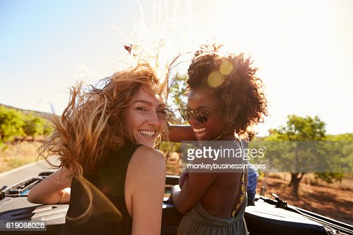 Two women standing in the back of open car turning : Foto de stock