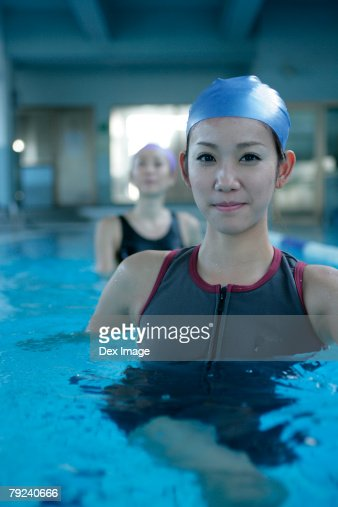 Two women standing in the swimming pool, close-up : Stock Photo