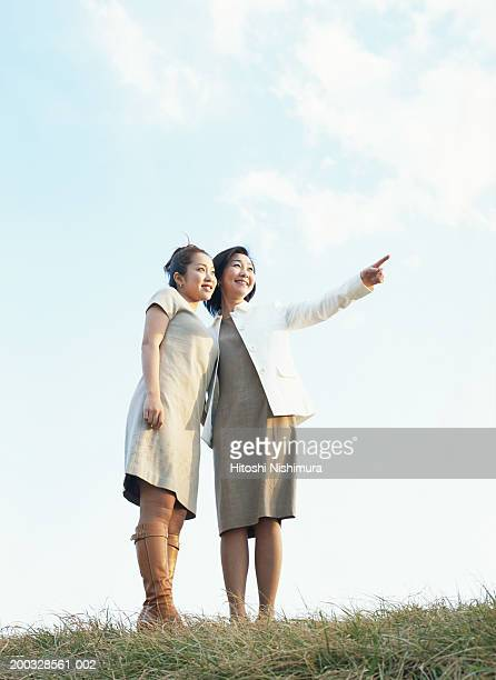 Two women standing on grass, looking away, low angle view
