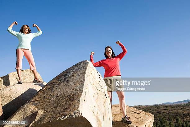 Two women standing on rocks, arms raised, smiling, portrait