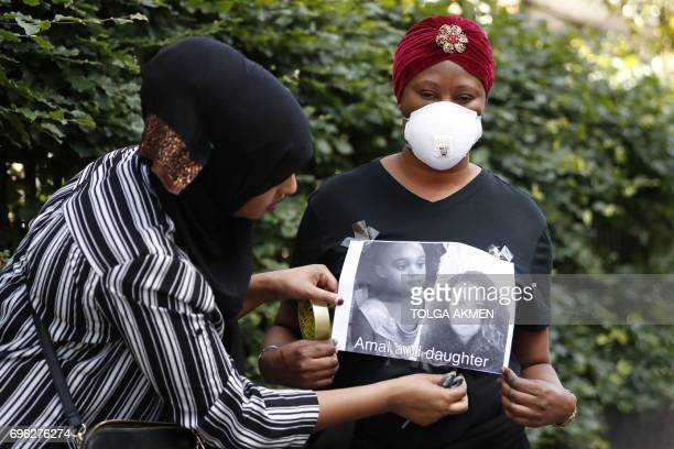 Two women stick a picture to her top of a mother and daughter missing following a huge fire at Grenfell Tower a residential tower block in west...