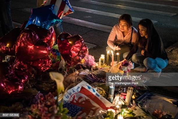 Two women stops to pay tribute at vigil along Las Vegas Boulevard near Mandalay Bay hotel on Wednesday October 4 in Las Vegas NV